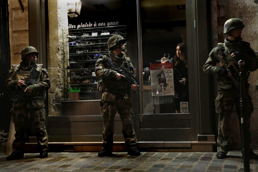 Parisian soldiers stand watch outside of a store after the terrorist attack.