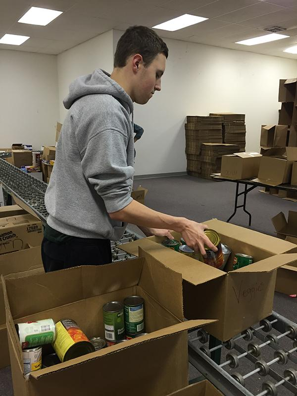 After collecting cans from classroom donations, alumnus Dean Wundrach sorts everything into boxes.
