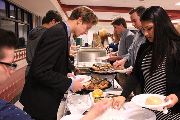 In the cafeteria, new National Honor Society members enjoy breakfast as part of the tapping ceremony.