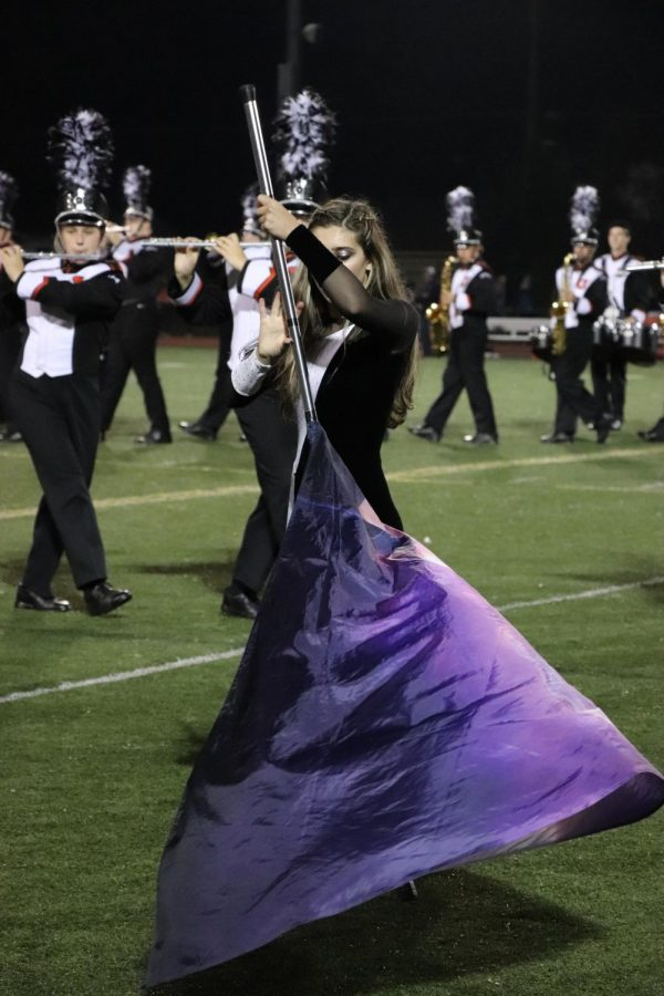 During halftime, junior Jayy Emery twirls her flag into a cone.