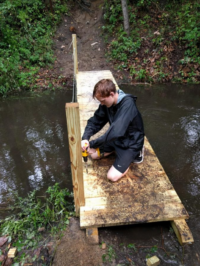 Picture of the student building a bridge across a small creek