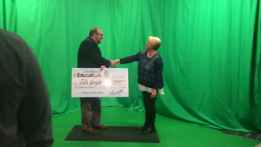 Teacher Julie Wright accepts a $1,500 check as her prize.