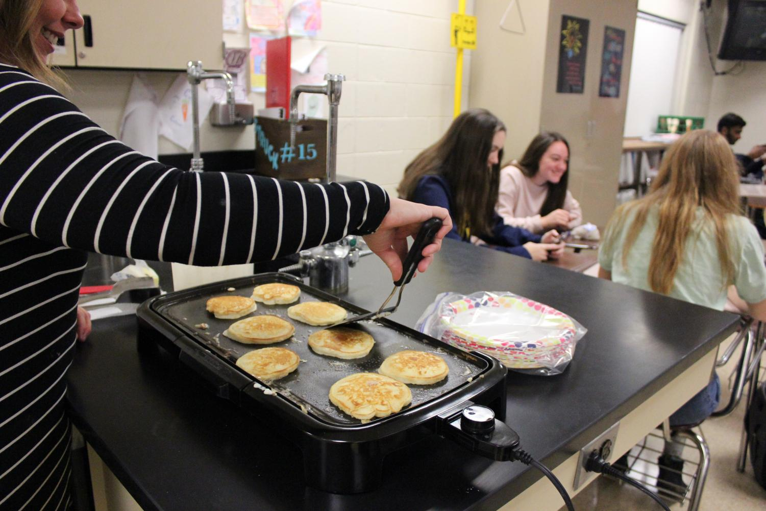 Teacher Courtney Struck makes pancakes for her first hour class celebrating mole day.