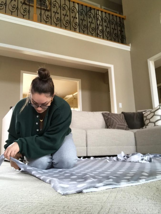 Senior Arianna Palushaj making blankets to donate to the project Linus Foundation.