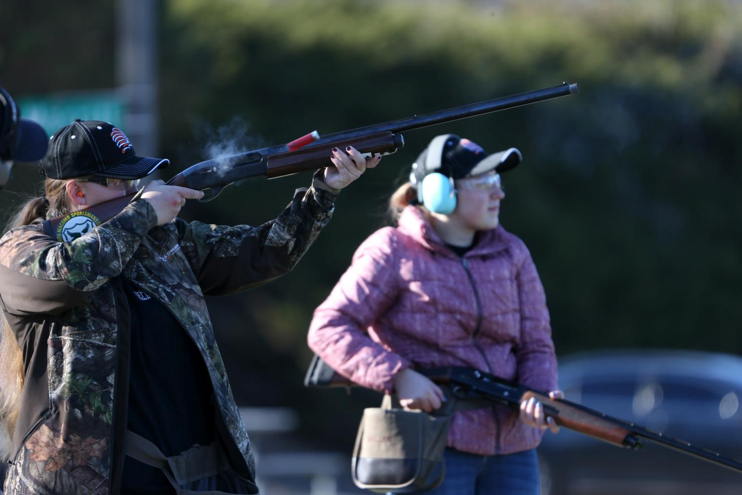 At the North Macomb Sportsmen's Club in Washington, sophomore Annie Grzeszczak takes down a clay target while sophomore Shelby Remeselnik waits for her next shot.