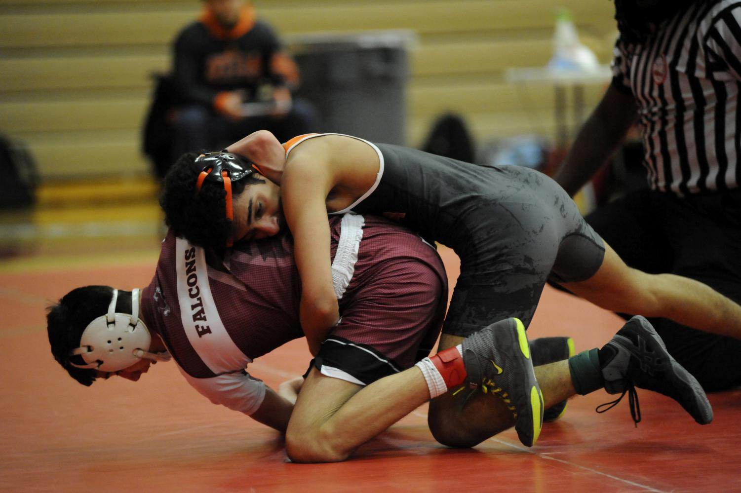 Sophomore Tahami Waris pins down a wrestler from Ford High school during a match.