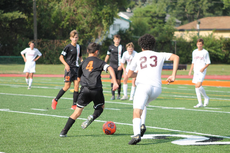 Freshman Luca Dedivinaj dribbles the ball up the field.