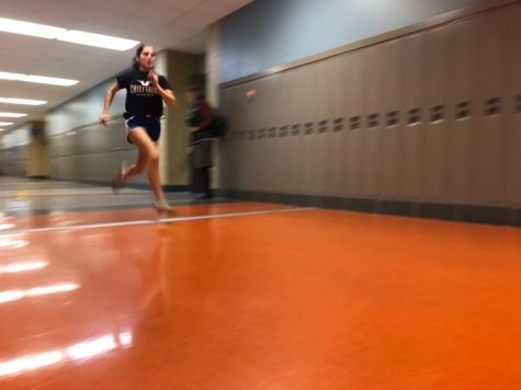 Junior Allison Mispelon dashes down the hall to increase her running time during speed club training.
