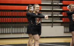 Junior Jenna Kilburg practices her cheer routine before the varsity team performs.