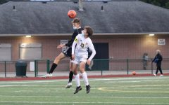 Junior Jack Mahoney goes up for a header against the opposing team.