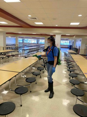 Custodian Liliana Djonovic wearing a Victory Electric Static Sprayer, using it to disinfect surfaces that are hard to get to.