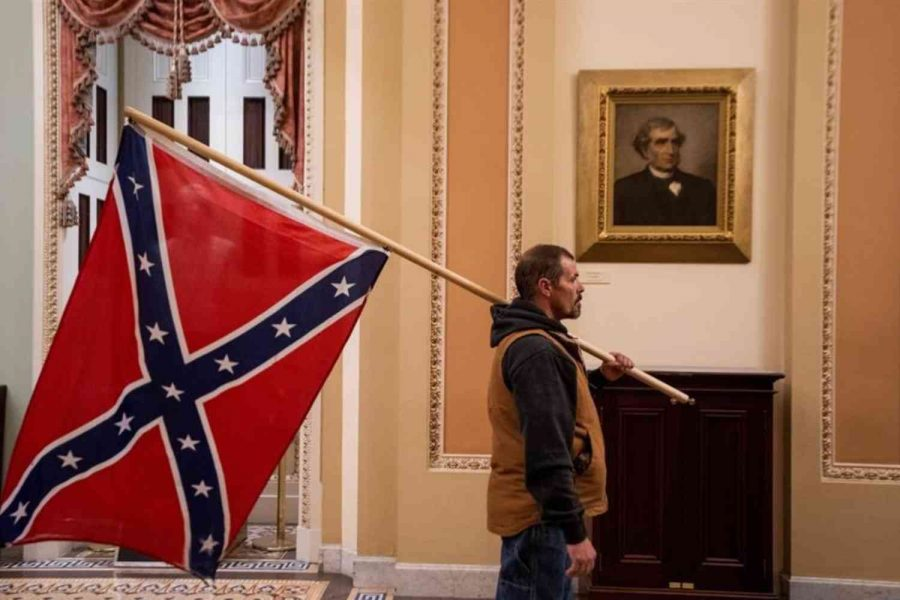 Trump supporter holds a Confederate flag outside the Senate Chamber during the Capitol Hill riot